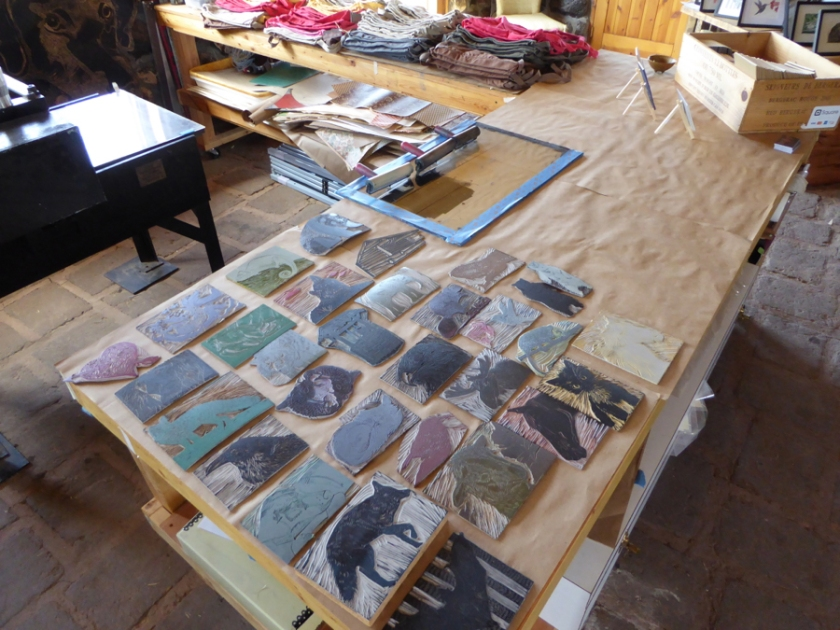 A variety of linocuts waiting for people to custom print their backpacks at Open Studio